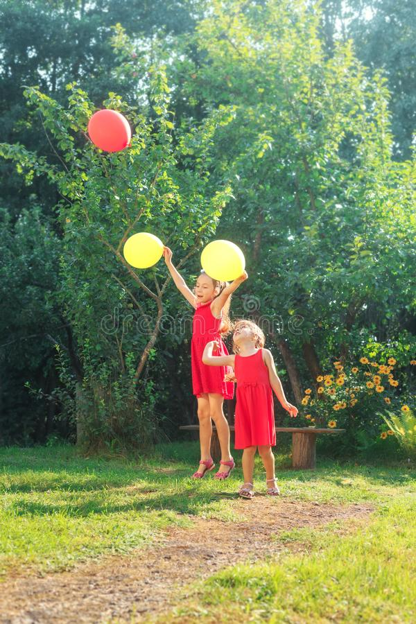Two happy cute little sisters jumping with colorful toy balloons outdoors. Smiling kids having fun in green spring garden at warm royalty free stock photos