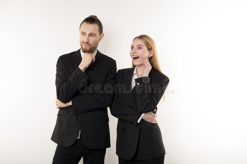 Two happy employees in black suits standing together with hands on waist looking at the presentation of their boss stock photo