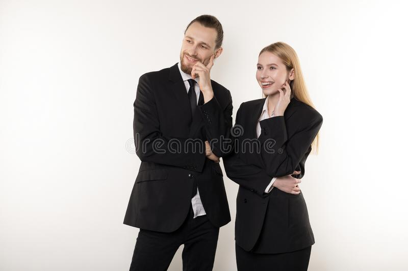Two happy employees in black suits standing together with hands on waist looking at the presentation of their boss royalty free stock image