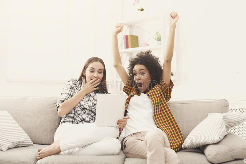 Two happy excited female friends using tablet. royalty free stock photo