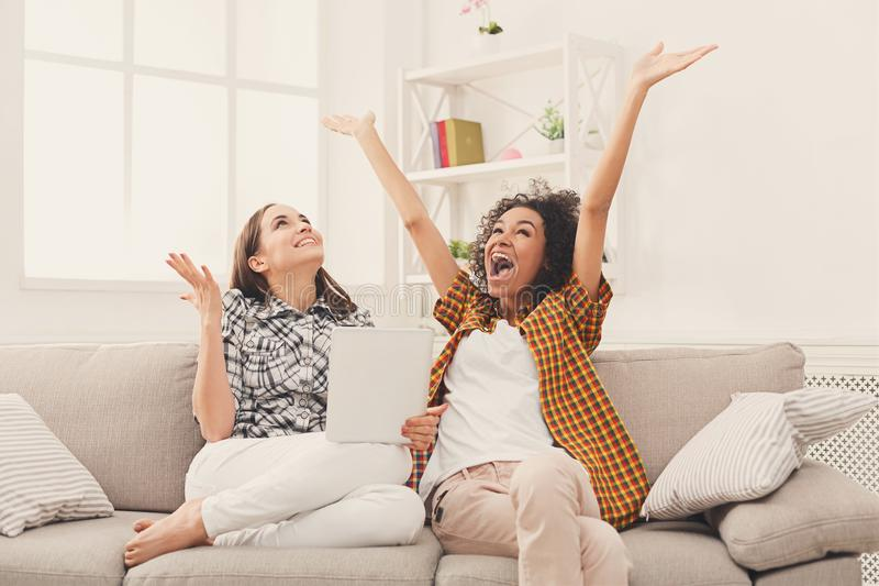 Two happy excited female friends using tablet. stock image