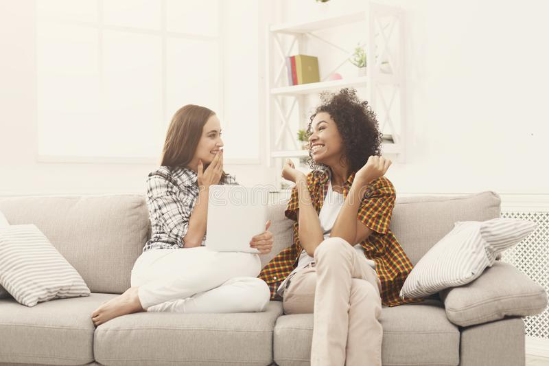 Two happy excited female friends using tablet. stock photography