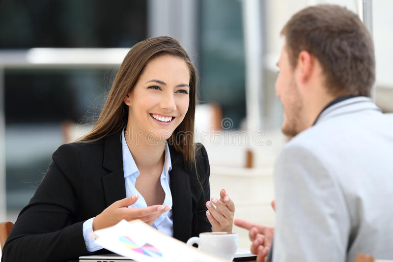 Two executives having a business conversation in a bar. Two happy executives meeting in a restaurant and having a business conversation stock photography
