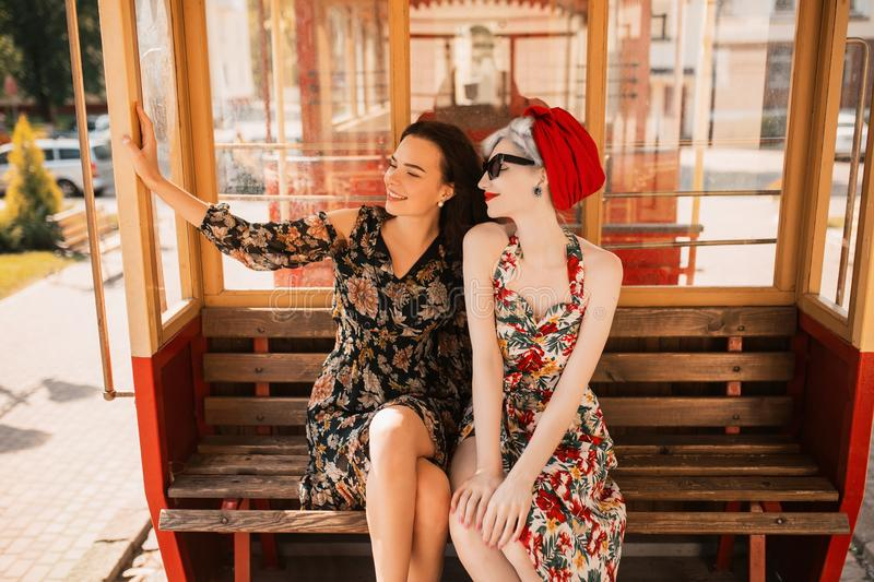 Two happy fabulous lesbian girls in flower dress enjoy journey in train. Tourist travel. Retro woman with pale skin and red lips. royalty free stock image