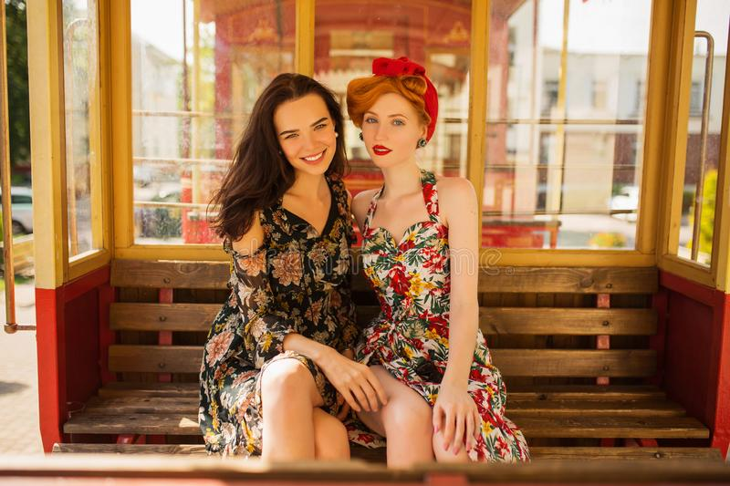 Two happy fabulous lesbian girls with long hair in flower dress on background of train. A beautiful retro woman with pale skin and stock photography