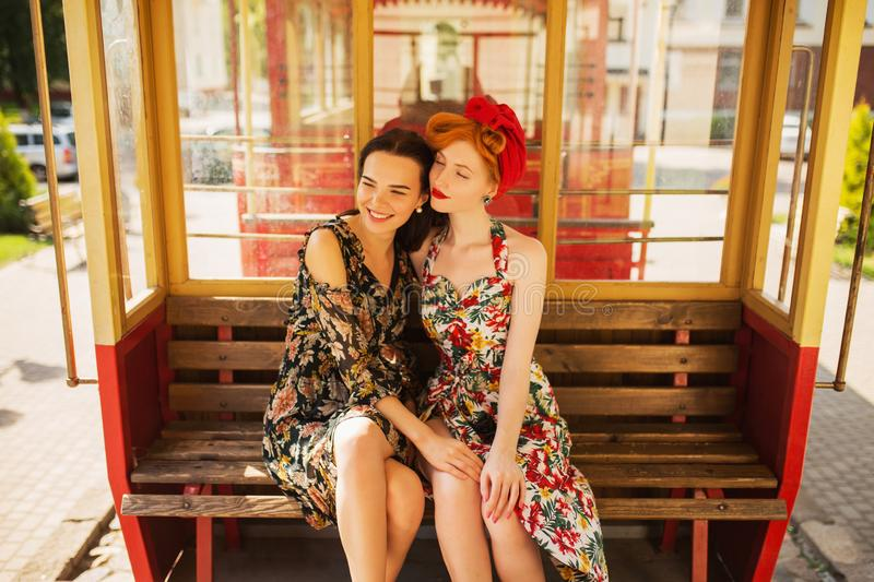 Two happy fabulous lesbian girls with long hair in flower dress on background of train. A beautiful retro woman with pale skin and stock photo
