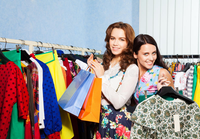 Two happy female friends with clothes in shop stock photos