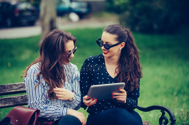 Two happy female friends laughing watching media content together in a digital tablet stock photo