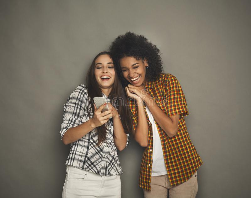 Two happy female friends using smartphone royalty free stock photo