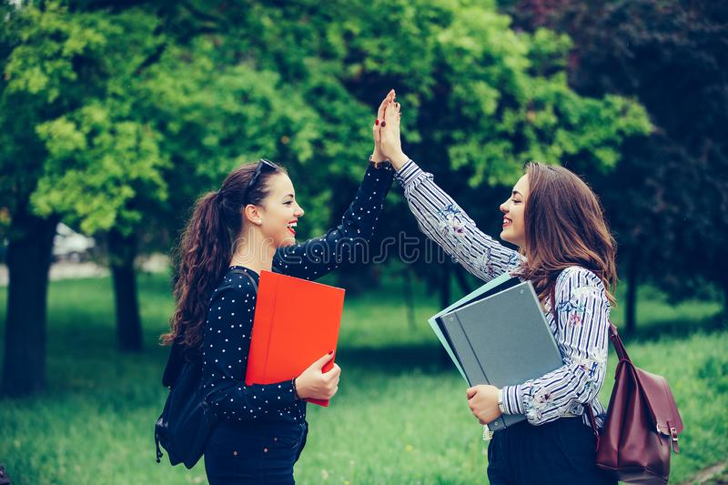 Two happy female students are giving high, celebrating success for approved exams in a park stock photography