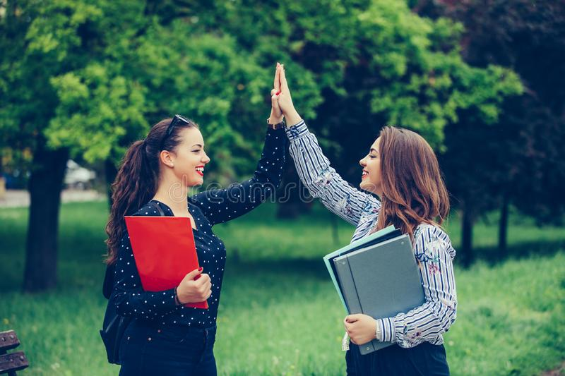 Two happy female students are giving high five after successfully learning. Two happy female students are giving high, celebrating success for approved exams royalty free stock photo