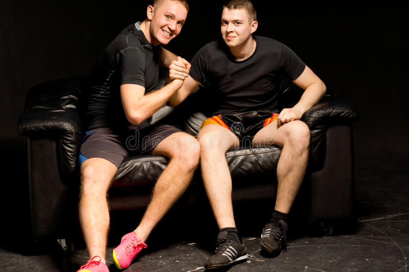 Two happy fit young men having an arm wrestle. Two happy fit young men having a friendly arm wrestle as they sit together on a black leather couch in the stock images