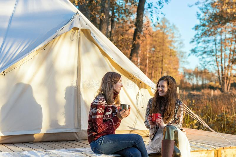 Two happy friends drinking coffee while relaxing near canvas bell tent royalty free stock images