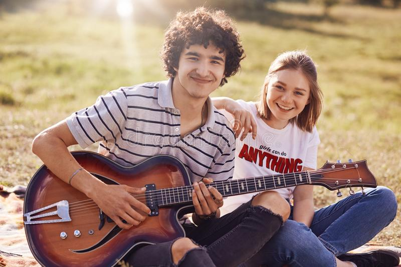 Two happy friends have joyful expression, gentle smiles on faces, recreat during summer time outdoor, play guitar and sing popular stock photo
