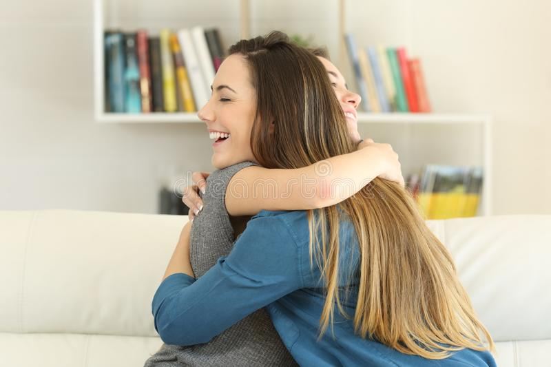 Two happy friends hugging at home royalty free stock photo