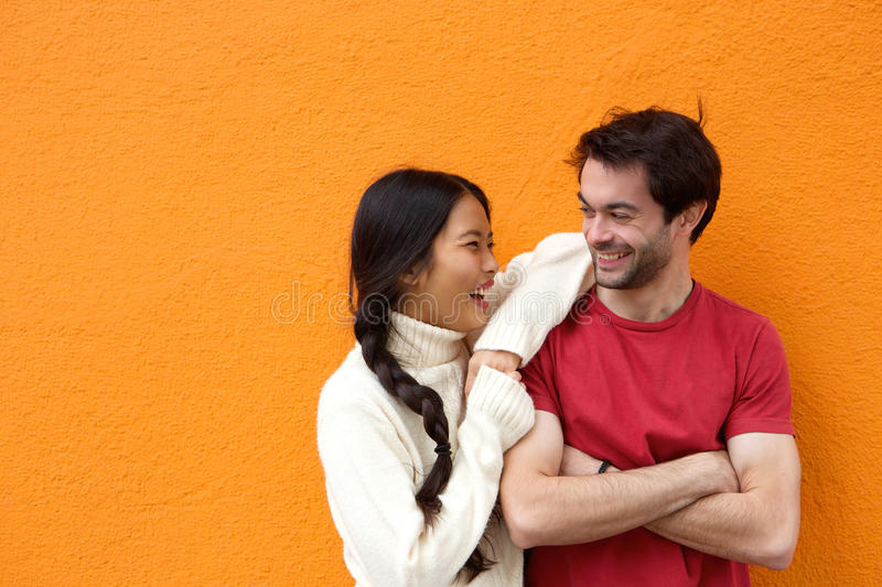Two happy friends laughing against orange background royalty free stock images