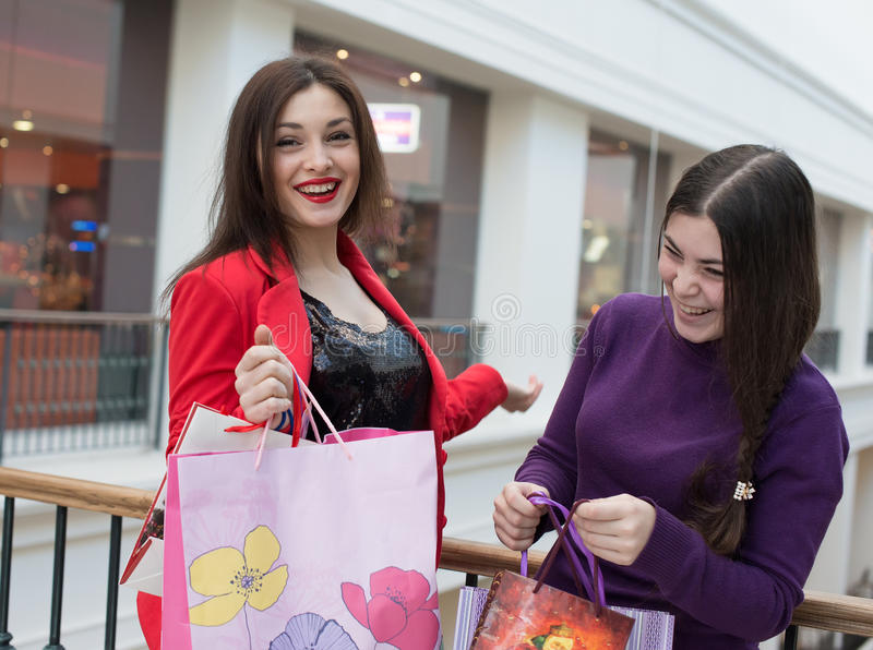 Two happy friends shopping in mall. Look at their purchase stock image