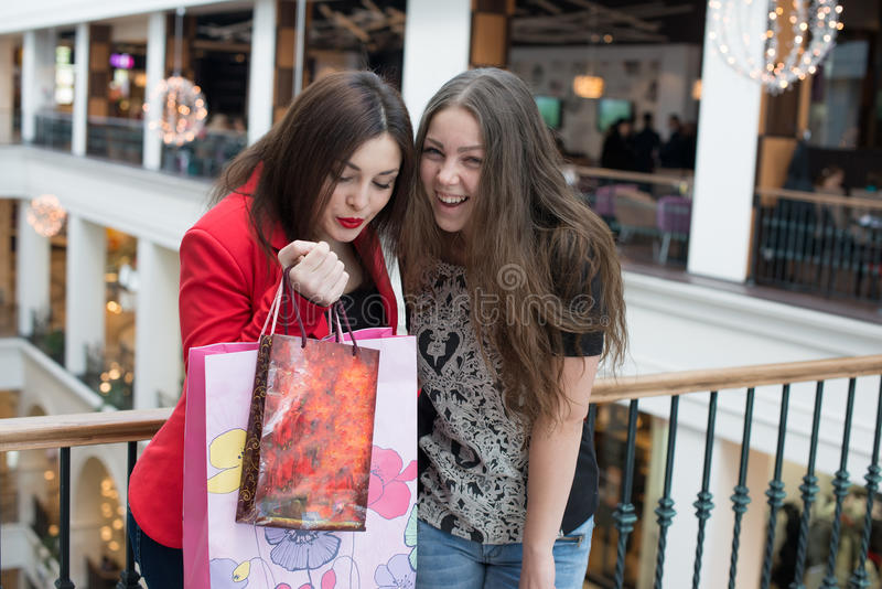 Two happy friends shopping in mall. Look at their purchase royalty free stock photos