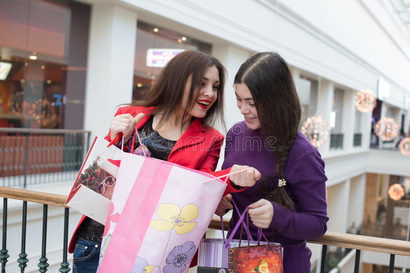 Two happy friends shopping in mall. Look at their purchase stock photography