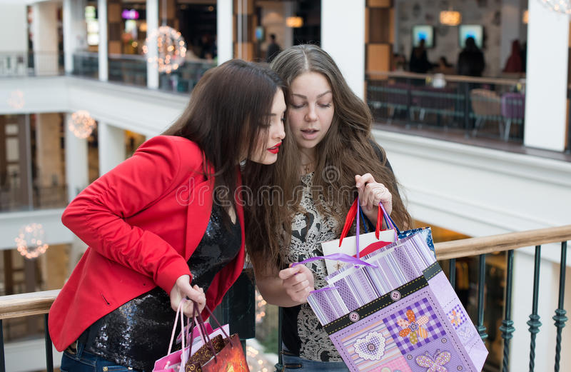 Two happy friends shopping in mall. Look at their purchase royalty free stock photo