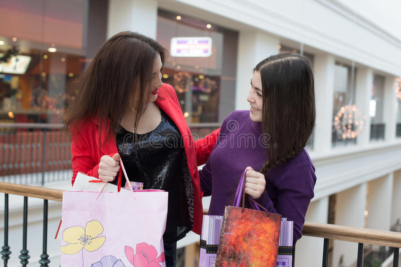 Two happy friends shopping in mall. Look at their purchase royalty free stock image