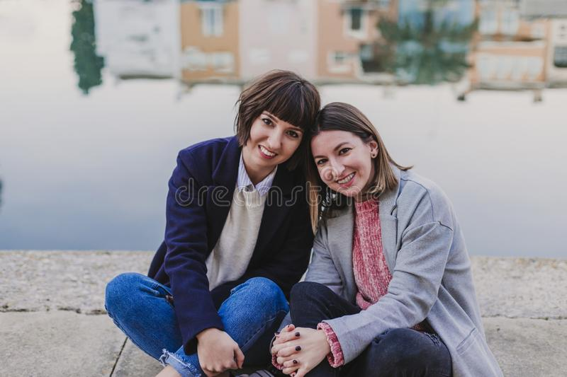 Two happy friends or sisters sitting on the floor and looking at the camera. Lifestyle outdoors. Port background. Friendship, outside, having, relationship stock photos