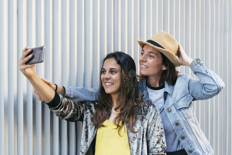 Two happy friends taking selfie in metallic and clean background stock photo