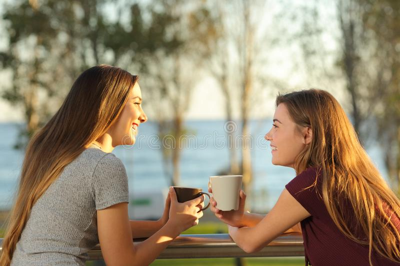 Two happy friends talking outdoors in a balcony. Two happy friends talking outdoors in an apartment balcony in the beach with the sea in the background stock photography