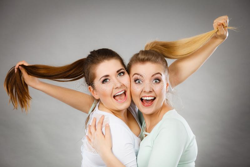 Two happy friends women hugging holding hair. Two happy friends women hugging, smiling with joy and holding their hair. Woman friendship and relationship royalty free stock photo