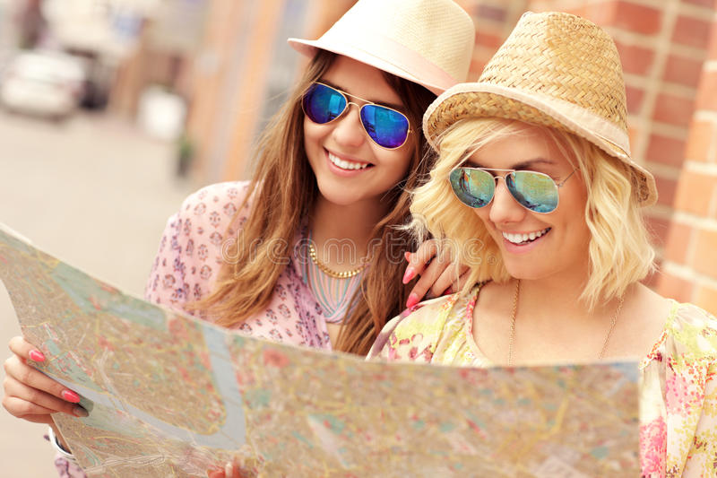 Two happy girl friends sightseeing the city royalty free stock photography