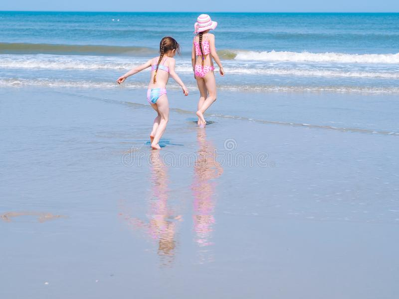 Two happy girl in swimsuit having fun on tropical beach and running in the water into the air on the sea coast at the day time stock images