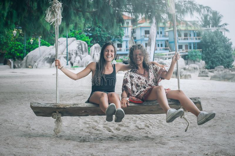 Two happy girlfriend swinging on the swing at tropical beach. Koh Tao, Thailand stock photography