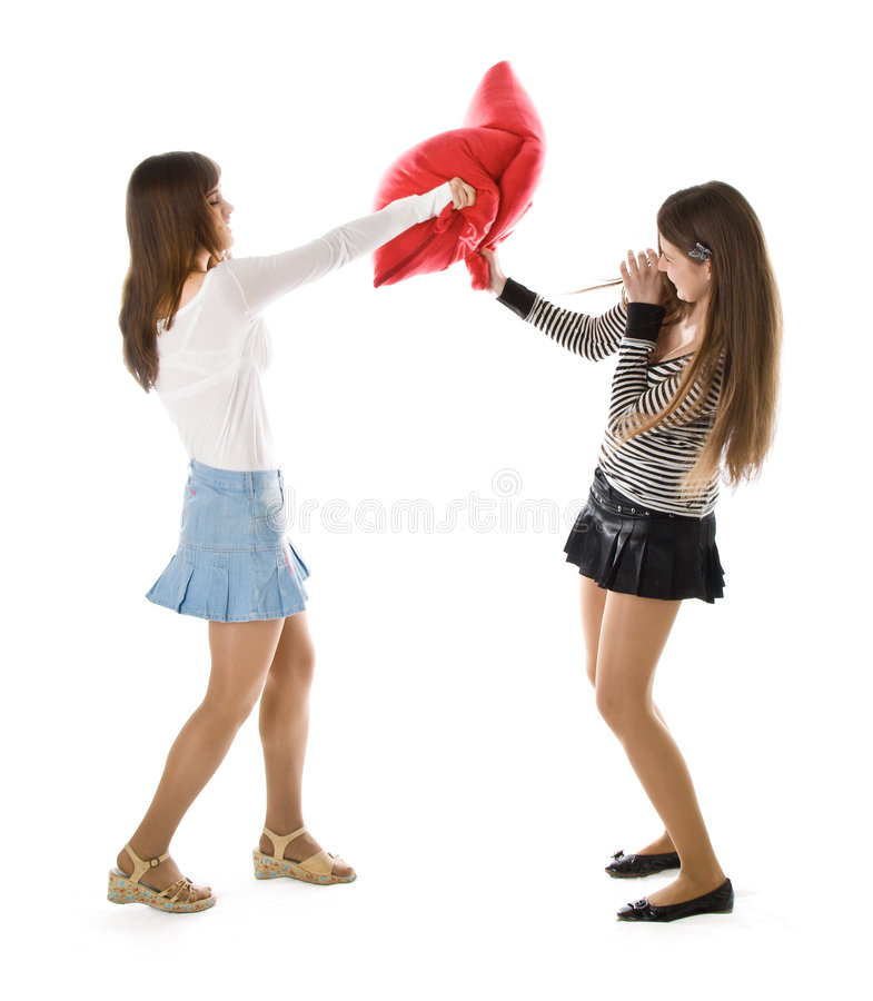 Two happy girlfriends fighting a pillows