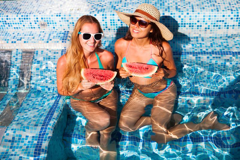 Girlfriends holds half a red watermelon over a blue pool, relax royalty free stock photos