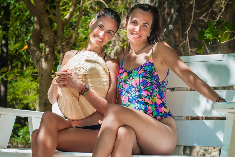 Two happy girlfriends smiling and enjoying on the beach stock image