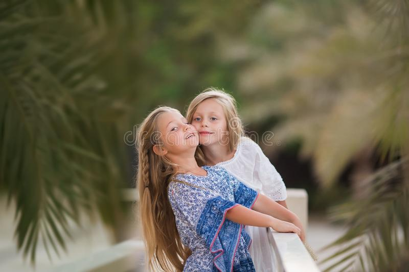 Two happy girls as friends hug each other in cheerful way. Little girlfriends in park. Children Friendship Together Smiling stock image