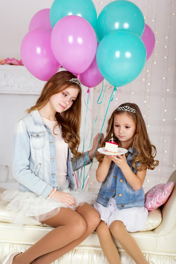 Two happy girls with birthday cake and balloons. Two pretty girls sisters are celebrating birthday in a studio with cake and blue and pink balloons royalty free stock image
