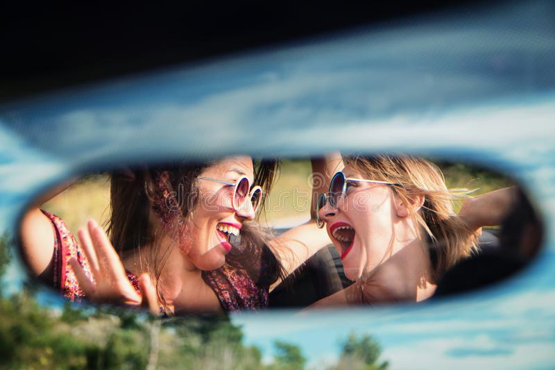 Two happy girls in a car rear-view mirror. royalty free stock photography