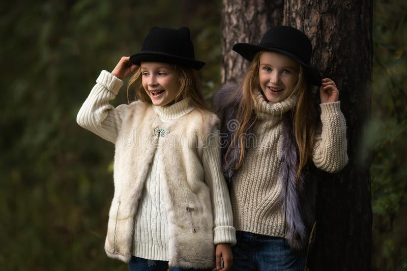 Two happy girls are equally dressed: in fur vests and hats in the forest. Little girlfriends in park. stock image