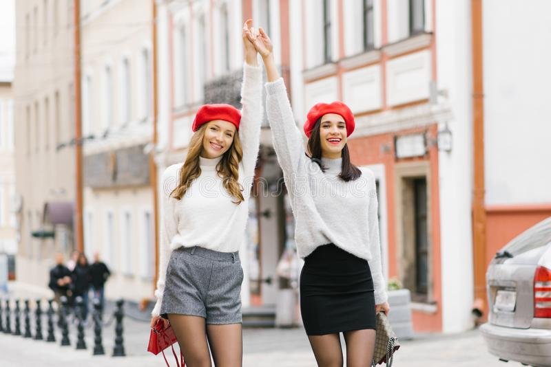 Two happy girls girlfriends hold hands and raised them up, they are smiling. Brunette and brown-haired woman in red berets stock photos