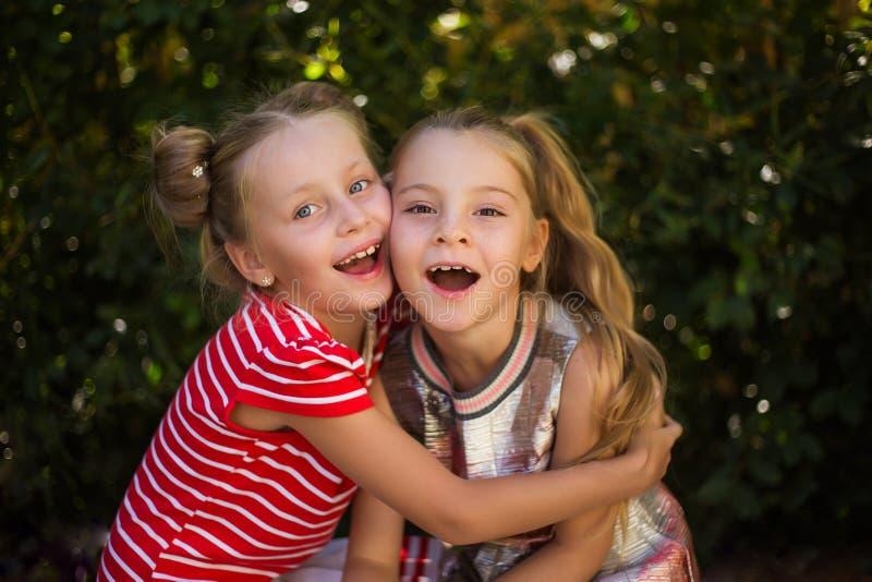 Two happy girls hugging girlfriend stock photo