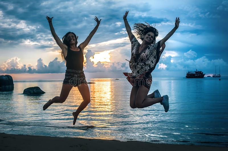 Two happy girls jumping at sunset on tropical beach royalty free stock photography