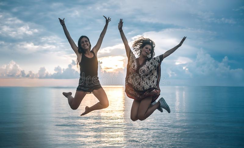 Two happy girls jumping at sunset on tropical beach. Koh Tao, Thailand royalty free stock photography