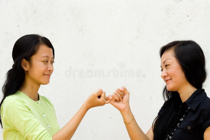 Two happy girls make peace to each other stock image