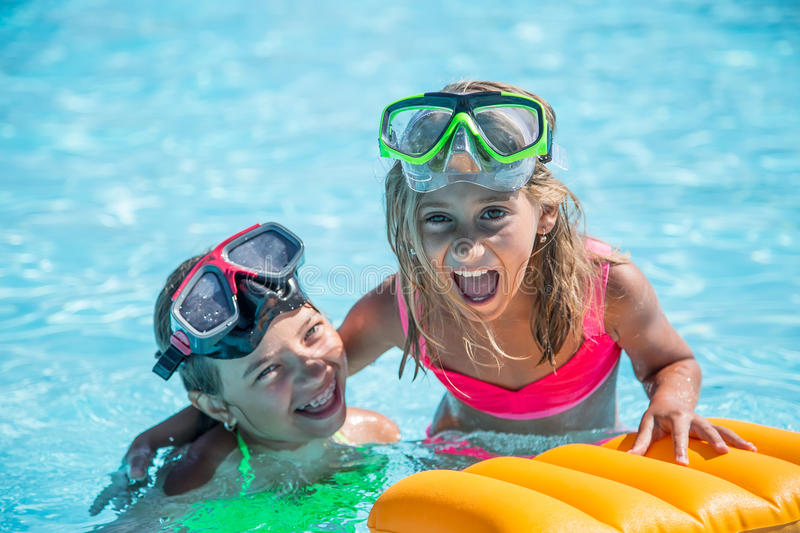 Two happy girls playing in the pool on a sunny day. Cute little girls enjoying holiday vacation royalty free stock image