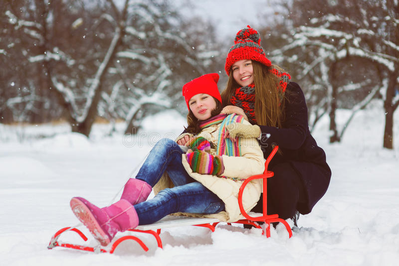 Two happy girls playing on the snow in winter day outdoor stock photos