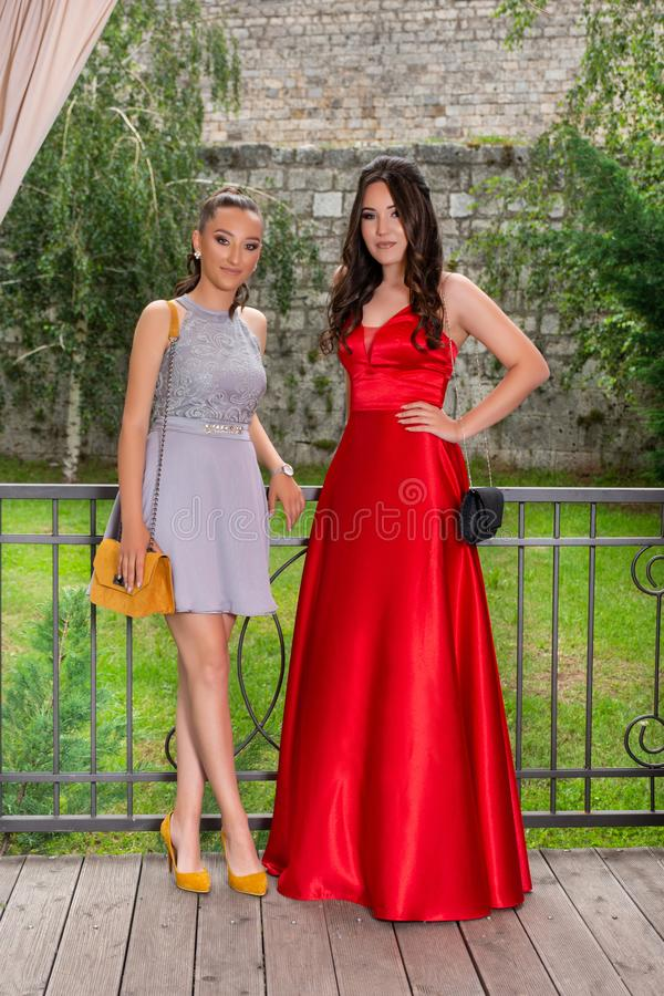 Two happy girls posing on a restaurant garden in front of the fence. Girls wear a red and gray elegant dress. Blurred wall background. Fashion concept. Close stock photo