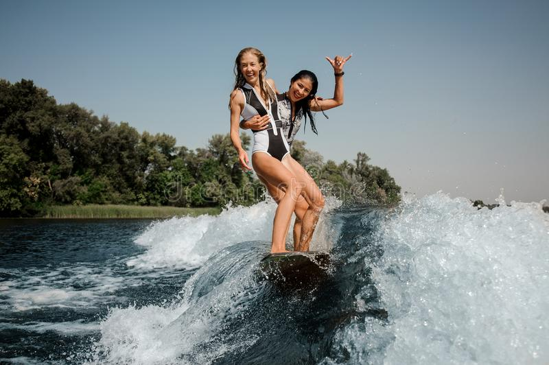 Two happy girls riding on the one wakeboard on the lake. Two happy girls in the black and white and red swimsuit riding on the one wakeboard on the lake stock images