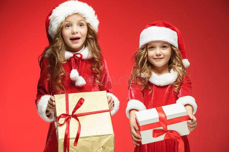 Two happy girls in santa claus hats with gift boxes at studio stock photography