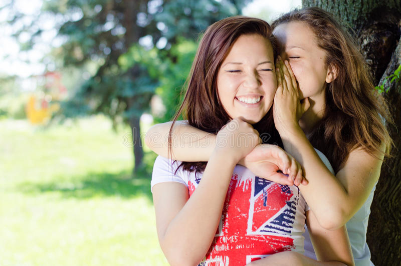 Two happy girls sharing gossip and laughing on green summer outdoors background stock photography